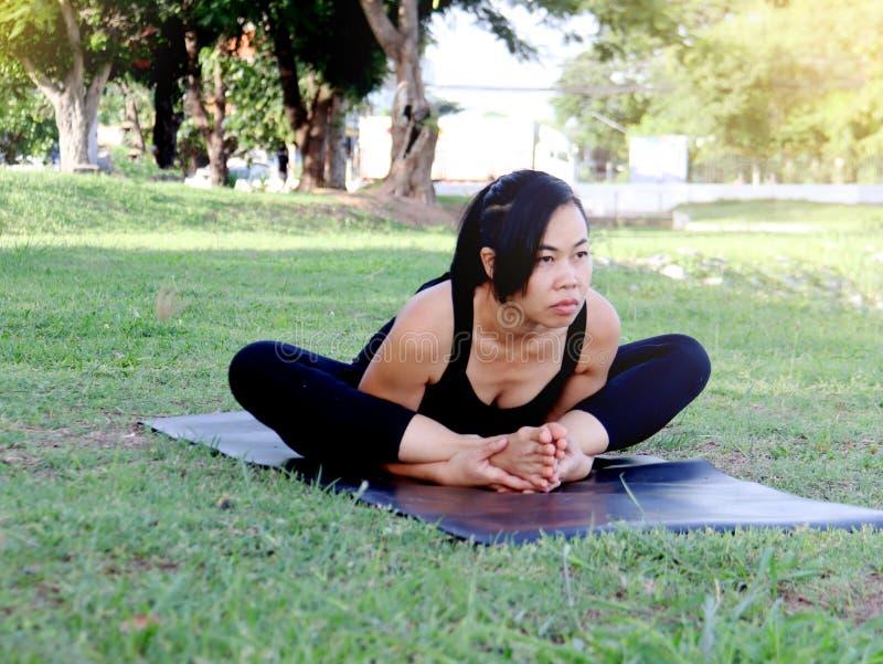 A borboleta asiática da prática da mulher levanta para a frente os braços da curvatura sob os pés fotos de stock royalty free
