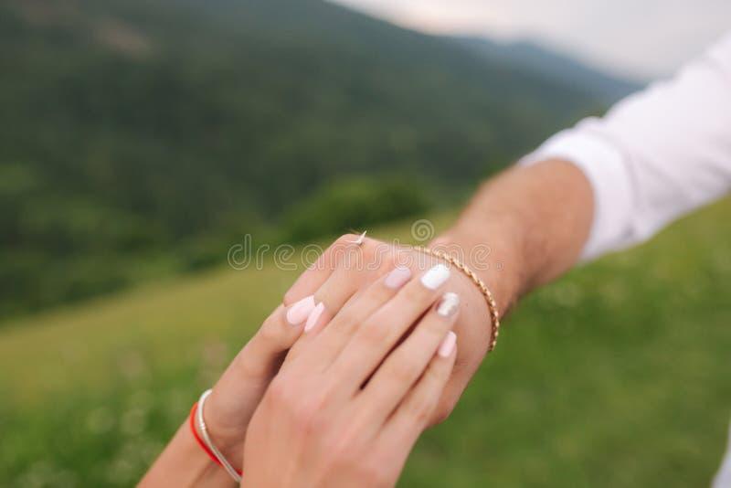 A borboleta em noivos entrega Feche acima das mãos dos pares fotos de stock