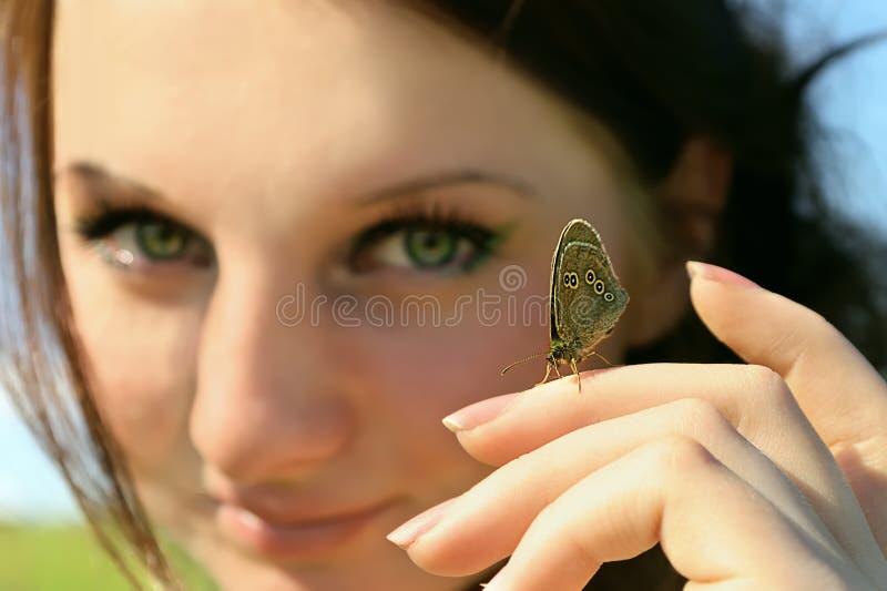 Borboleta na mão da mulher com a face no fundo imagens de stock royalty free