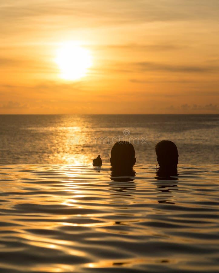 Piscine de bord d'infini avec la mer sous le coucher du soleil photos stock