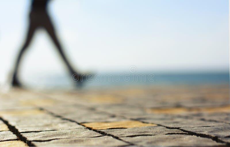 Bord de la mer de marche brouillé d'againts de silhouette d'hommes image stock