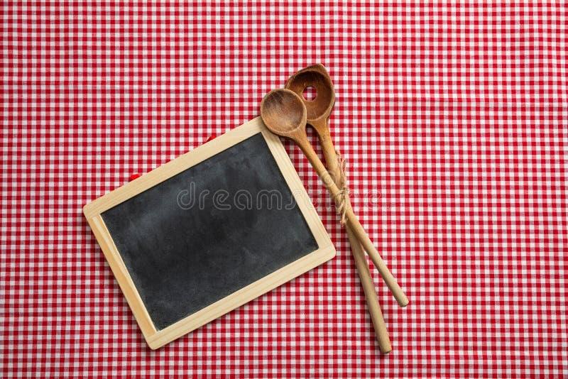 Bord en houten keukengerei op rood geruit picknicktafelkleed, ruimte voor tekst stock afbeeldingen