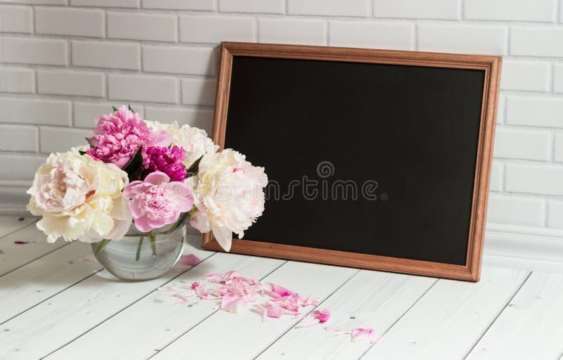 Bord en pioenen in vaas stock afbeelding
