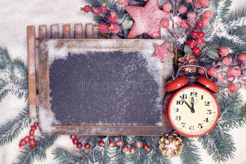 Bord met Kerstmisdecoratie en wekker op sneeuw stock fotografie