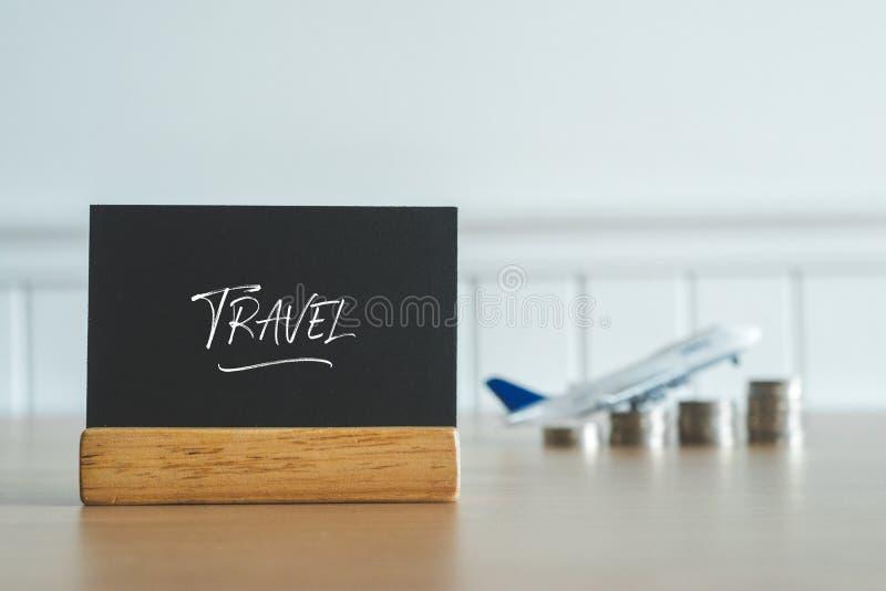 Bord met muntstukkengeld en vliegtuig op achtergrond op de rechterkant De tekst van het reisbericht royalty-vrije stock afbeelding
