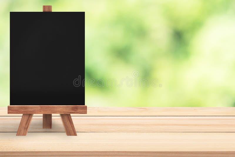 Bord met schildersezel bovenop houten lijst Groene aard bokeh op de achtergrond royalty-vrije stock foto's
