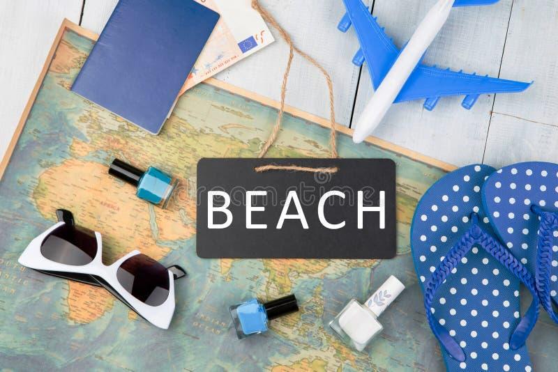 bord met tekst & x22; BEACH& x22; , vliegtuig, kaart, paspoort, geld, ploffen stock foto's
