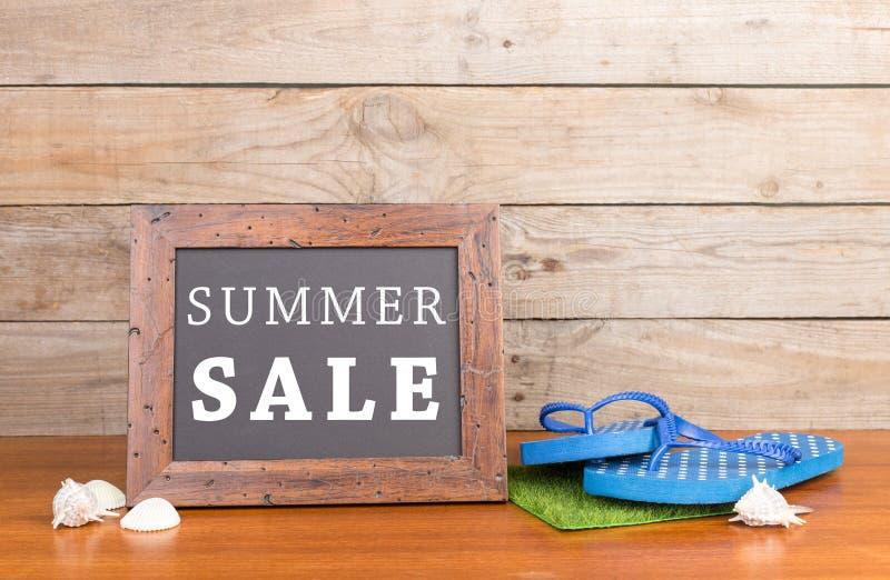 bord met tekst & x22; De zomer SALE& x22; , ploffen, zeeschelpen op bruine houten achtergrond royalty-vrije stock fotografie