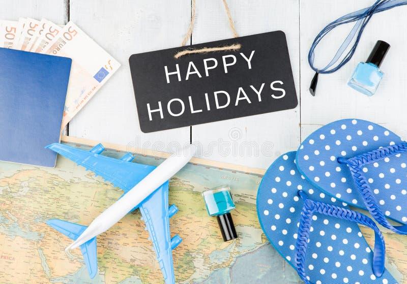 bord met tekst & x22; GELUKKIGE HOLIDAYS& x22; , vliegtuig, kaart, paspoort, geld, ploffen en andere toebehoren royalty-vrije stock foto's