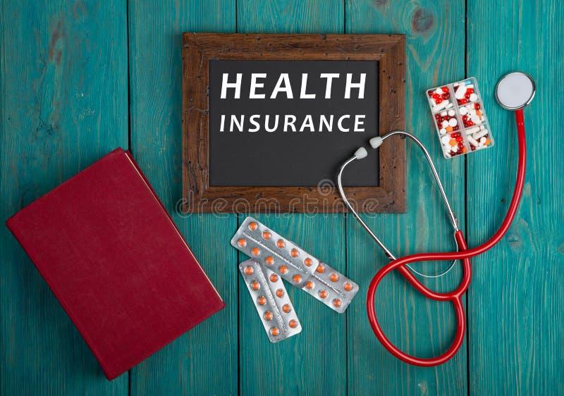 Bord met tekst & x22; Gezondheid insurance& x22; , boek, pillen en stethoscoop op blauwe houten achtergrond royalty-vrije stock afbeelding