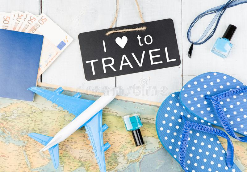 bord met tekst & x22; IK HOUD VAN AAN TRAVEL& X22; , vliegtuig, kaart, paspoort, geld, ploffen en andere toebehoren royalty-vrije stock afbeelding