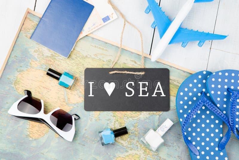 bord met tekst & x22; Ik houd van SEA& x22; , vliegtuig, kaart, paspoort, geld, ploffen en andere toebehoren stock foto's