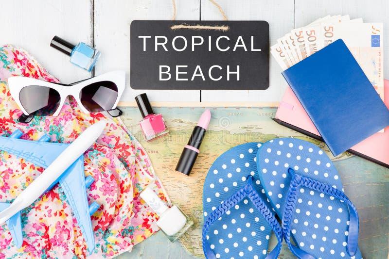 bord met tekst & x22; TROPISCHE BEACH& x22; , vliegtuig, kaart, paspoort, geld, zonnebril, ploffen en andere toebehoren stock fotografie