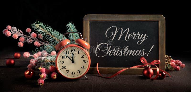 Bord met wekker en Kerstmisdecoratie op zwarte royalty-vrije stock foto