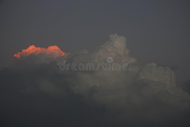 A borda da nuvem de tempestade escura é iluminada pelo raio do sol do por do sol Conceito da esperança fotografia de stock royalty free