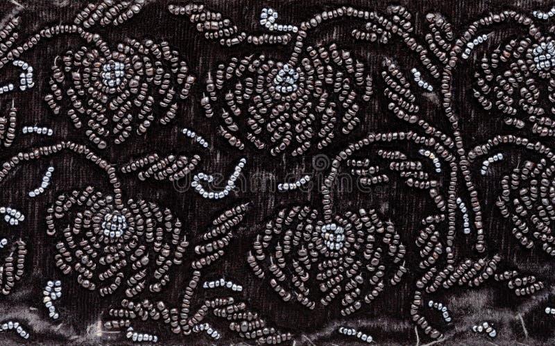 Bordado del vintage por las gotas negras en el terciopelo negro imagen de archivo