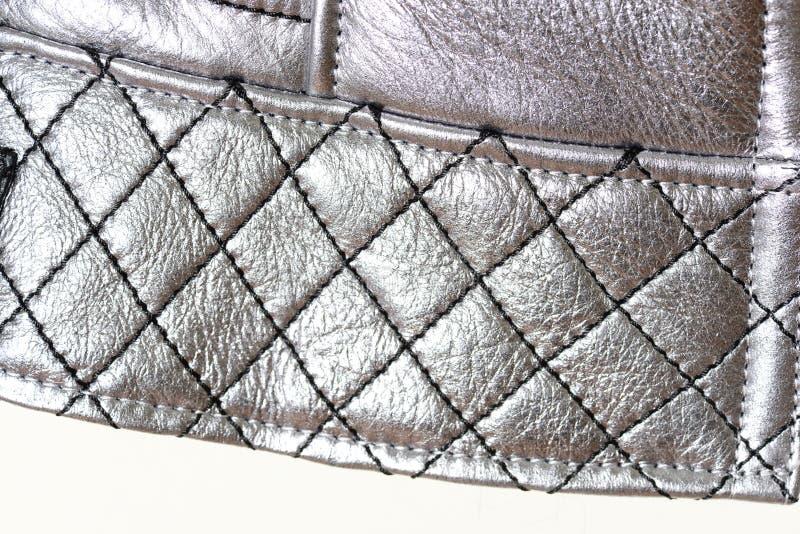 Borde acolchado de la torsión con las costuras bajo la forma de rejilla, fondo Color plata de la ropa Macro fotos de archivo libres de regalías
