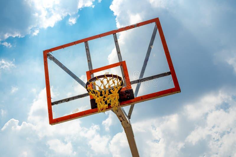 Borde de acero del baloncesto con el tablero trasero de acrílico transparente y la red plástica anaranjada de la cuerda imagenes de archivo