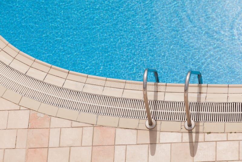Borde de la piscina de lujo hermosa con la escalera de las barras de gancho agarrador Visión superior foto de archivo libre de regalías