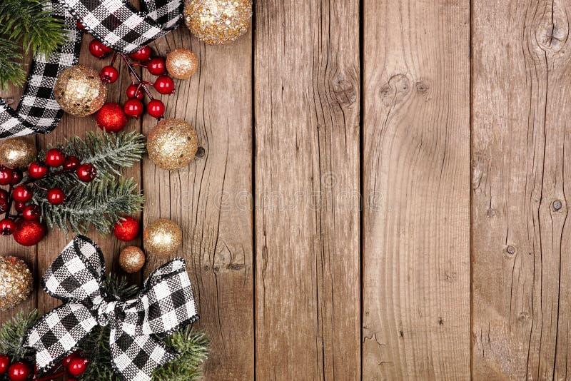 Borde del lado navideño con cinta de plástico blanco y negro, adornos y ramas, sobre un fondo rústico de madera. fotos de archivo
