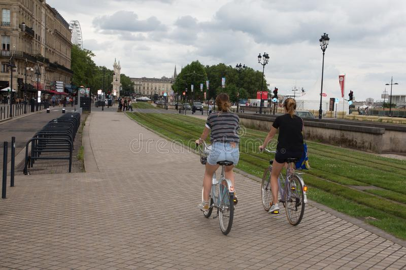 Bordeaux, Aquitaine / France - 06 10 2018 : two young girls are doing bikes cycling on the quays of Bordeaux royalty free stock photos