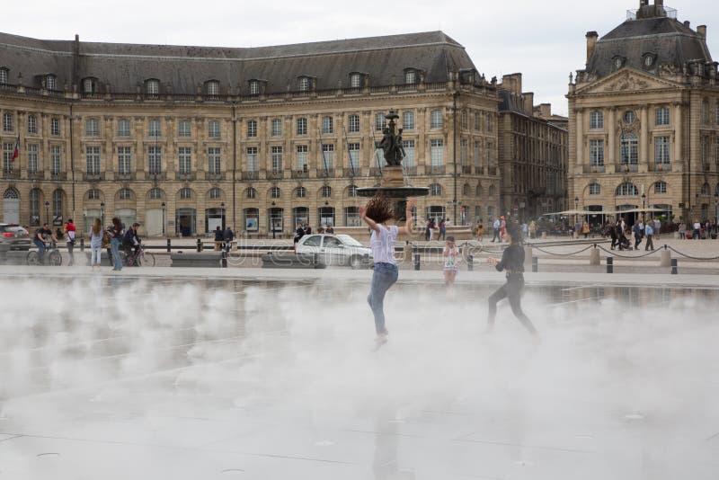 Bordeaux, l'Aquitaine/France - 06 10 2018 : fille dansant et éclaboussant le miroir de la bourse en place de l'eau au Bordeaux, image stock