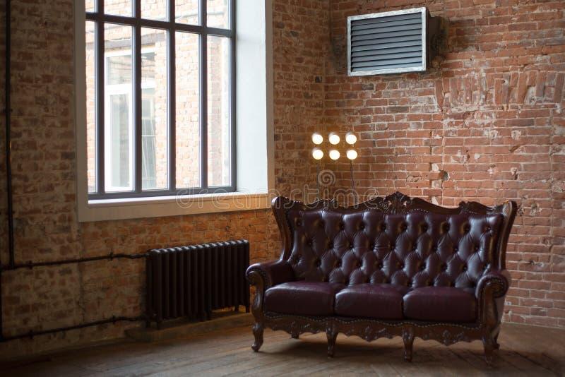 Bordeaux piskar soffan till vinden en inre med en ljus str?lkastare och ett f?nster red med den vita skarven forntida svin-j?rn b royaltyfri bild