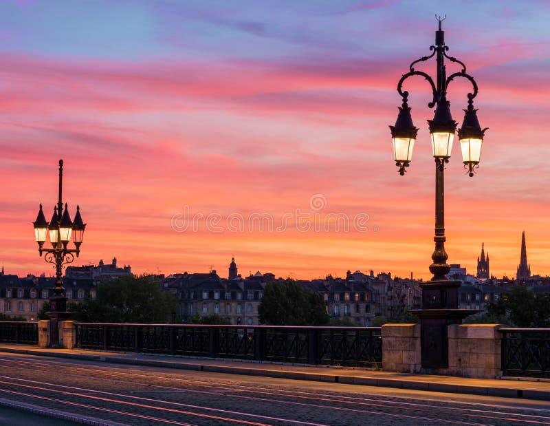 Bordeaux stenbro med härliga streetlights och att förbluffa solnedgånghimmel över den Bordeaux staden, Frankrike royaltyfri fotografi