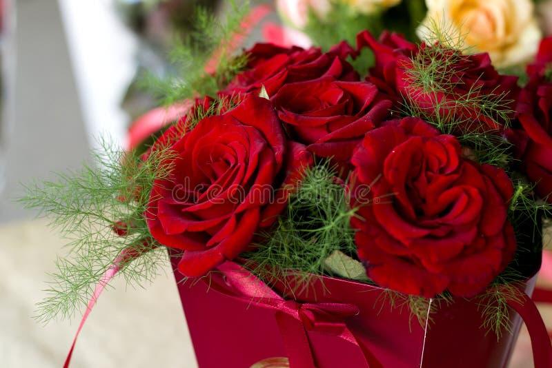 Bordeauxrosennahaufnahme Blumenstrauß von Burgunder-Rosen in einer roten Geschenkbox stockfoto