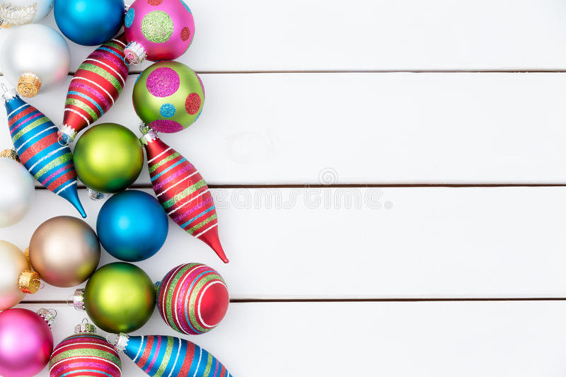 Border of assorted colorful Christmas ornaments. Border of assorted colorful Christmas tree ornaments with spindles and baubles arranged on white wooden boards royalty free stock image