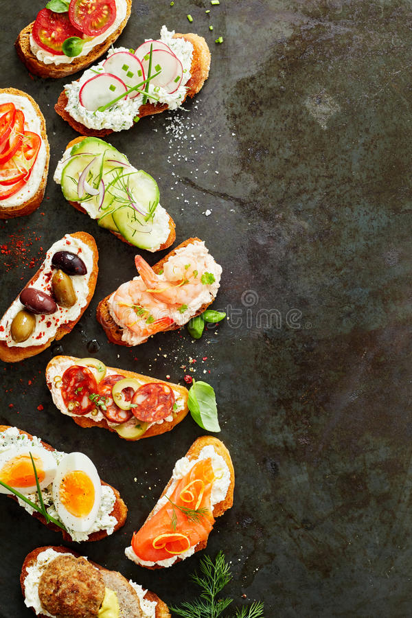 Border of assorted fresh canapes or bruschetta stock photo