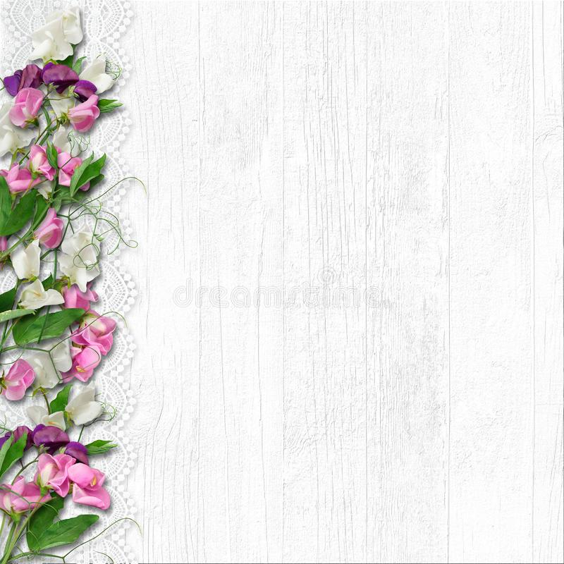 Border of beautiful spring flowers on a white wooden background. Vintage white wooden background with border of beautiful spring flowers, with a place for photos stock photo