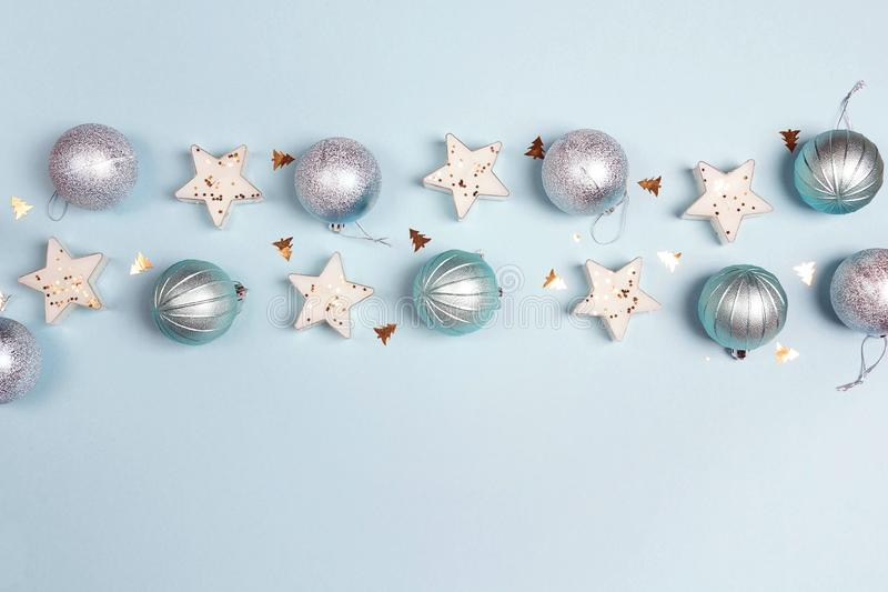 Border of blue Christmas decorations with copy space on blue background. Top view, flat lay royalty free stock image