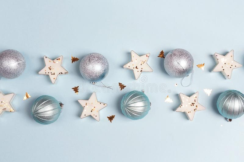 Border of blue Christmas decorations with copy space on blue background. Top view, flat lay stock photography