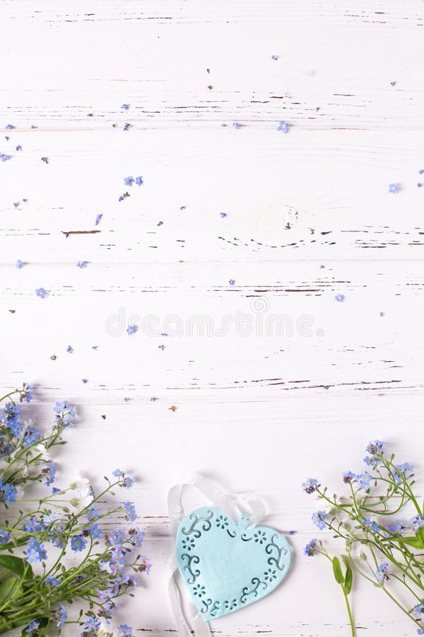 Border from blue forget-me-nots or myosotis flowers and heart royalty free stock photo