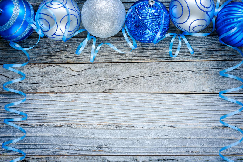 Border of Christmas Balls. Border of Christmas blue and silver balls on top of an old wooden board, top view. Copy space for text royalty free stock photos