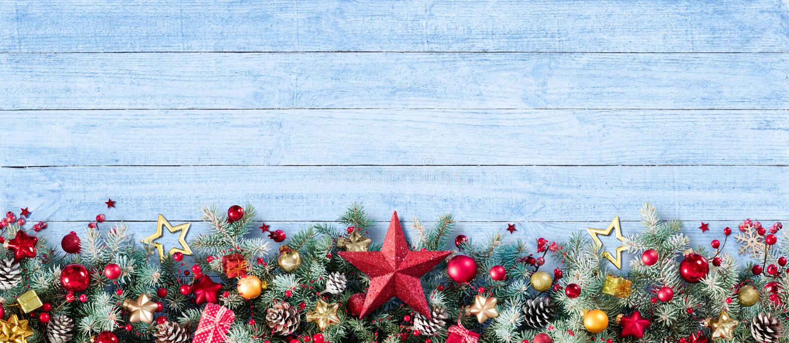 Border Of Christmas Decoration Of Fir Branches And Baubles. On Plank stock photos