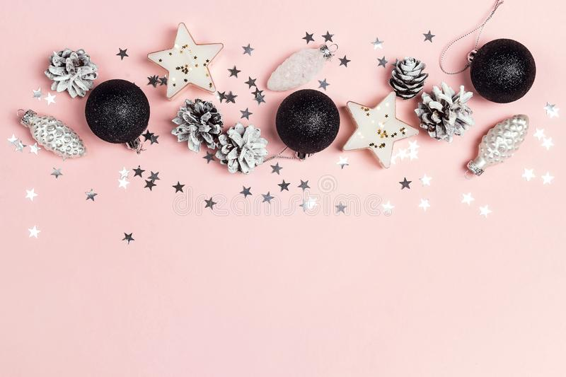 Border of Christmas decorations and copy space on a pink backgr. Ound. Composition of cones, black balls,candles and stars. Top view, flat lay royalty free stock photography