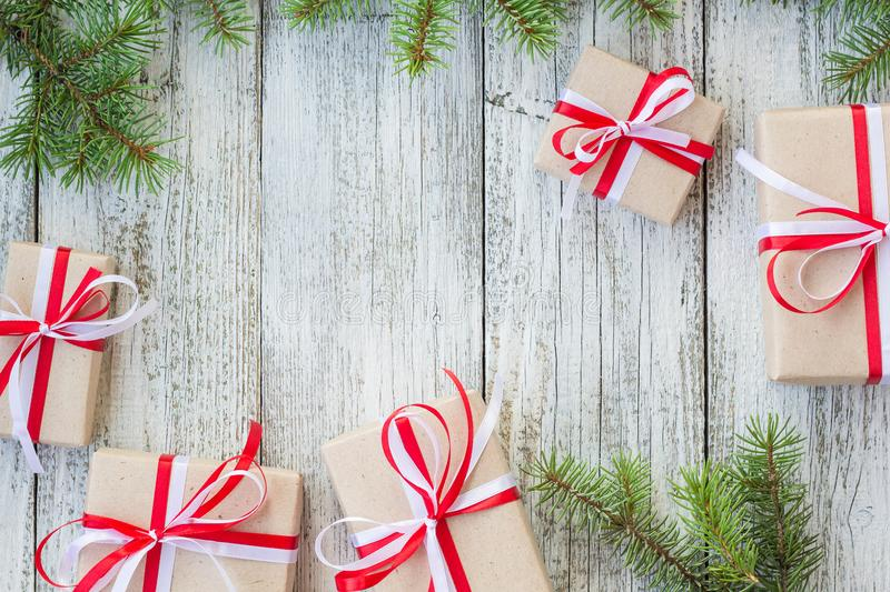Border of Christmas gift boxes and fir tree branch on wooden table. Top view with copy space royalty free stock photo
