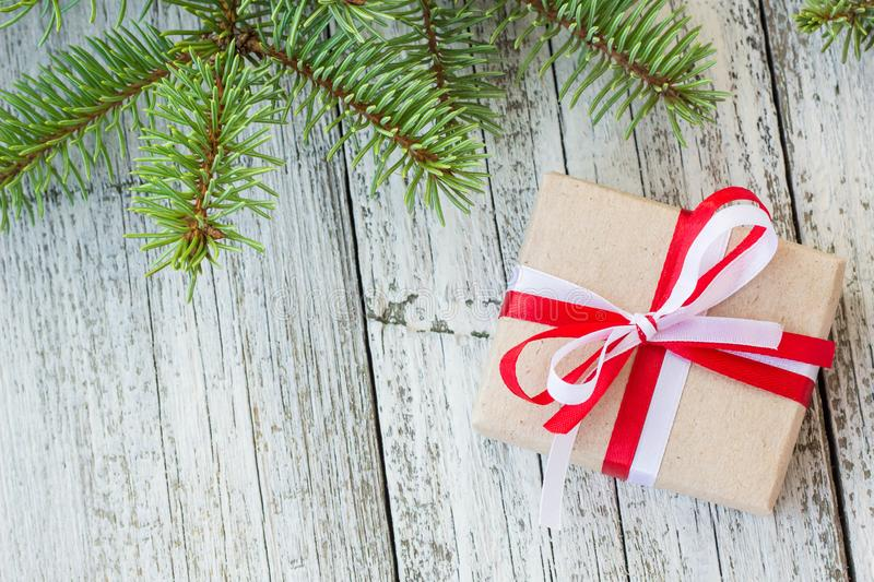 Border of Christmas gift boxes and fir tree branch on wooden table. Top view with copy space stock photography