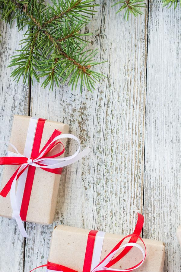 Border of Christmas gift boxes and fir tree branch on wooden table. Top view with copy space royalty free stock images