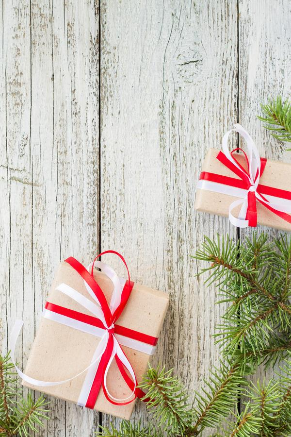 Border of Christmas gift boxes and fir tree branch on wooden table. Top view with copy space stock image