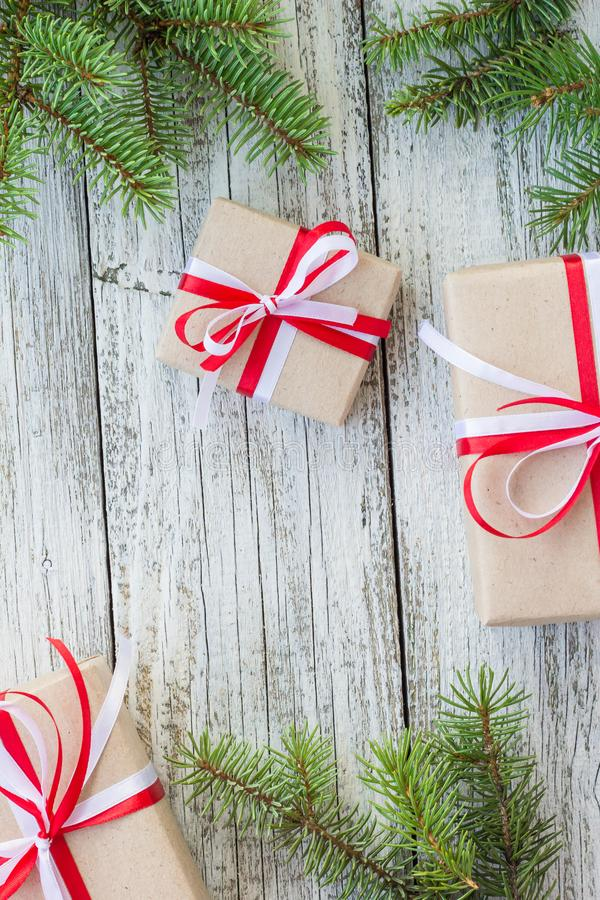 Border of Christmas gift boxes and fir tree branch on wooden table. Top view with copy space stock photo