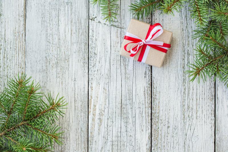 Border of Christmas gift boxes and fir tree branch on wooden table. Top view with copy space stock images