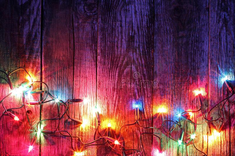 Border of christmas lights. On wooden background royalty free stock photo