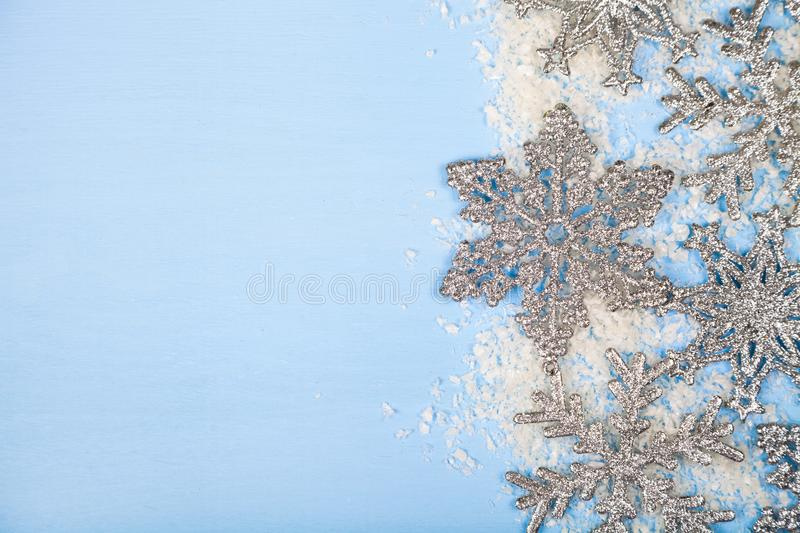 Border of Christmas snowflakes and snow. On a blue wooden background. Christmas decor royalty free stock images
