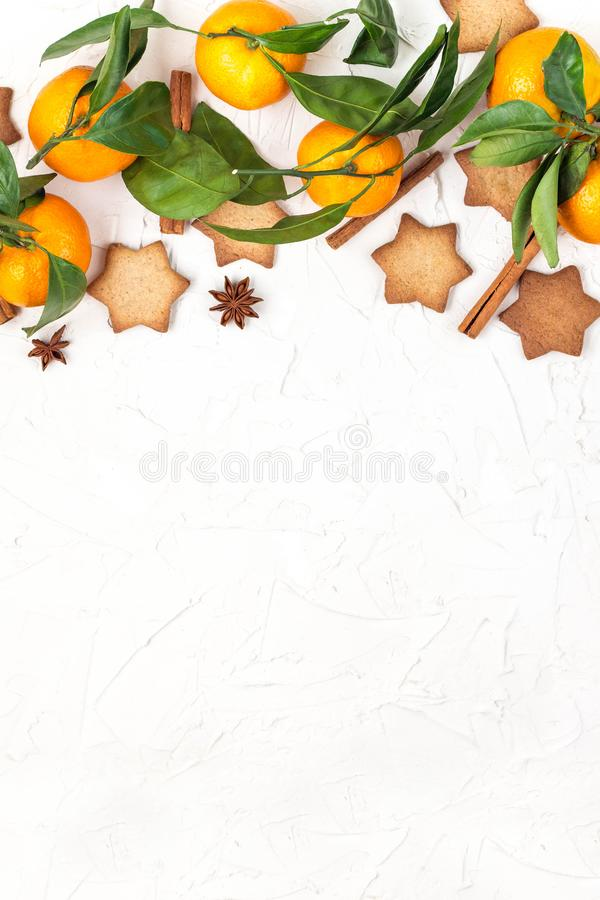 Border of Christmas star cookies with spices and mandarin on white background with copyspace. Top view royalty free stock photo