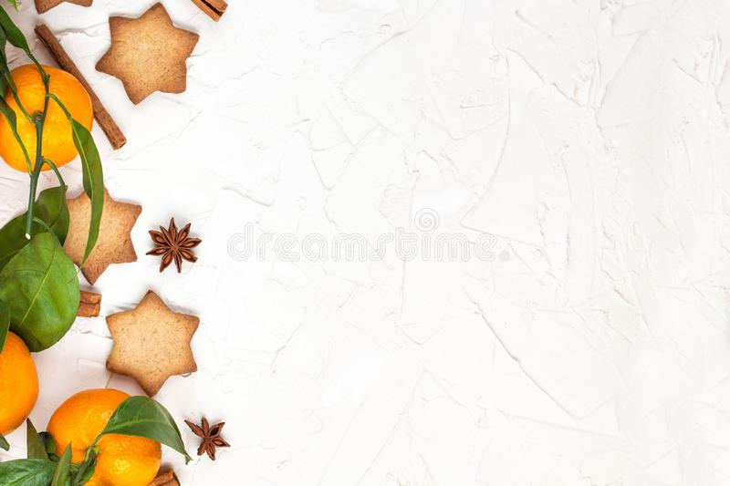 Border of Christmas star cookies with spices and mandarin on white background with copyspace. Top view royalty free stock image