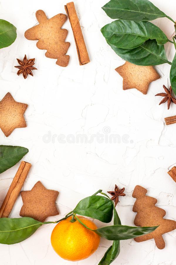 Border of Christmas star cookies with spices and mandarin on white background with copyspace. Top view stock photo
