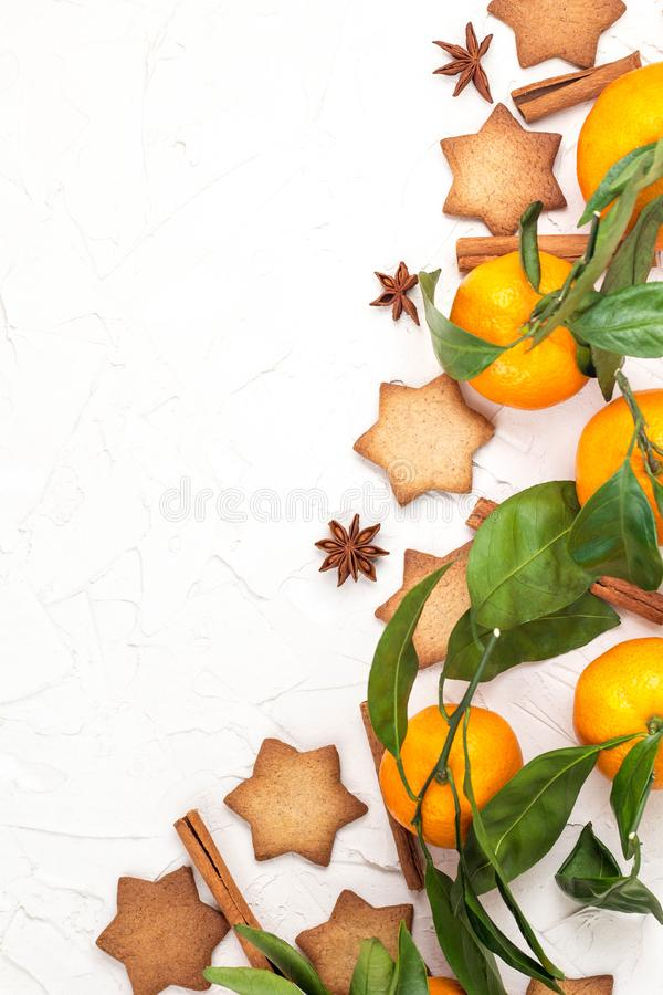 Border of Christmas star cookies with spices and mandarin on white background with copyspace. Top view stock image